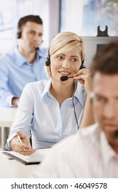 Young female customer service operator talking on headset, smiling.