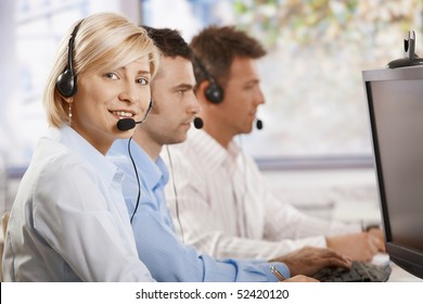 Young female customer service operator talking on headset, looking at camera, smiling.