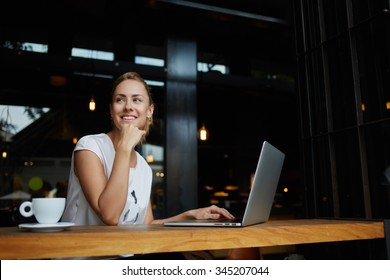 Young female with cute smile sitting with portable net-book in modern coffee shop interior during recreation time, charming happy woman student using laptop computer to prepare for the course work