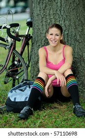 Young female cyclist resting with bike behind her in park - smiling