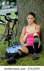 Young female cyclist resting with bike behind her in park