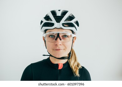 Young female cyclist stares at camera in clear glasses and while helmet in front of white wall