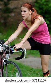 Young female cyclist stretching after ride