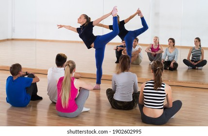 Young female dance teacher demonstrates new position to teenage students