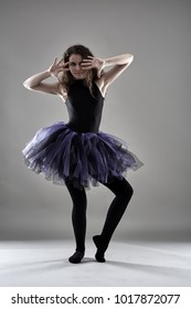 Young female dancer in full length against gray background