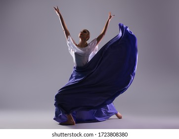 Young female dancer in long dress dance against gray background