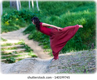Young female dancer moves on an old brick bridge  She balances on one foot