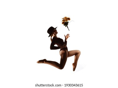 A young female dancer is seen on a stage with  a white background behind her. She leaps up  high and throws around a bouquet of flowers.