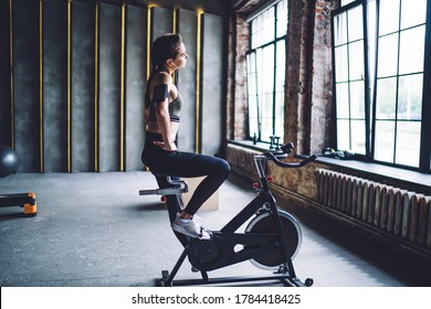 Young female with dark hair braid in sportswear with armband doing cardio training on stationary bicycle in loft industrial style gym
