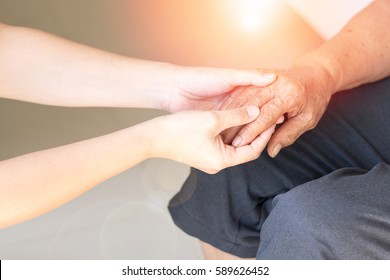 Young female daughter hands holding elderly aging old grandmother hand to support/comfort her with lens flair effect. World Elder Abuse Awareness Day, Disability caregiver healthcare concept