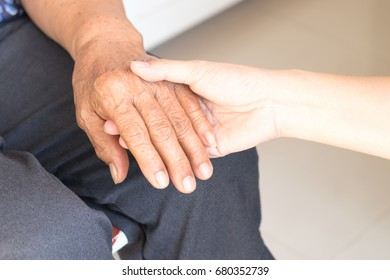 Young female daughter hands holding elderly aging old grandmother hand to support/comfort her