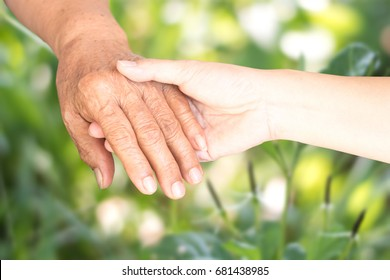 Young female daughter hands holding elderly aging old grandmother hand to support/comfort her with blurry nature light background. World Humanitarian Day. National Senior Citizens Day