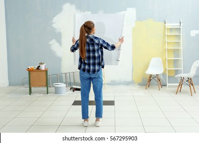 Young female decorator with drawing in empty room