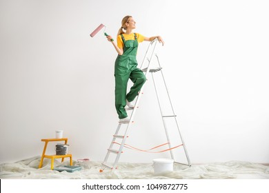 Young female decorator with paint roller in empty room