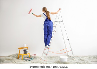 Young female decorator painting wall in empty room