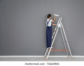 Young female decorator painting wall in room while standing on ladder