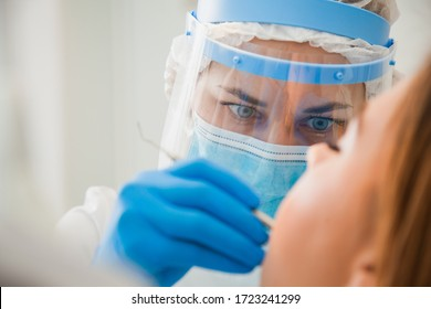 Young female dentist curing patient's teeth filling cavity. Stomatologist working with professional equipment in clinic office. Close-up shot, teeth care and medicine concept