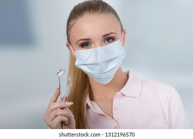 young female dentist with dental face mask holds dental instruments