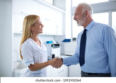 Young female dentist and patient are shaking hands in a dental office