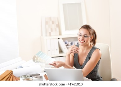 Young female designer working at office with laptop and color swatch