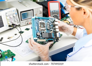 Young female digital electronic engineer examining computer PC motherboard in laboratory