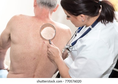 Young female doctor checking skin of senior patient