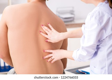 Young female doctor chiropractor massaging male patient