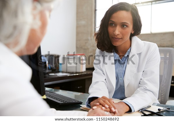 Young female doctor in consultation with senior patient