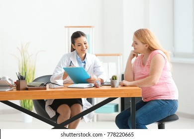 Young female doctor consulting overweight woman in clinic
