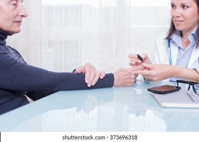 Young female doctor doing test with strips for an old diabetic patient while sitting at table