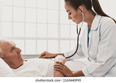Young Female Doctor Examining Senior Patient. Young Woman Doctor Wearing White Coat Examining Senior Man lying on Bed by using Stethoscope in Hospital. Healthcare Medicine Concept