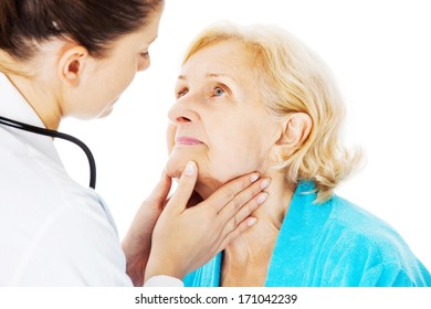 Young female doctor examining senior woman's throat isolated over white background