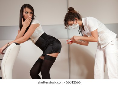 Young female doctor giving a needle shot to a sexy patient