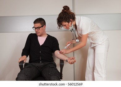 Young female doctor giving a needle shot to a scared guy