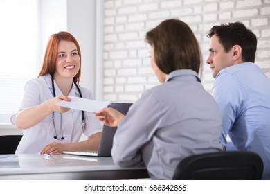 Young Female Doctor Giving The Prescription Paper To The Patient In Clinic