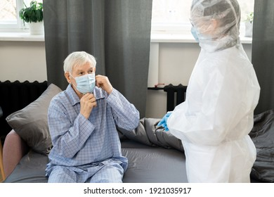Young female doctor in gloves and coveralls standing in front of sick senior man sitting on bed and putting on protective mask on his face