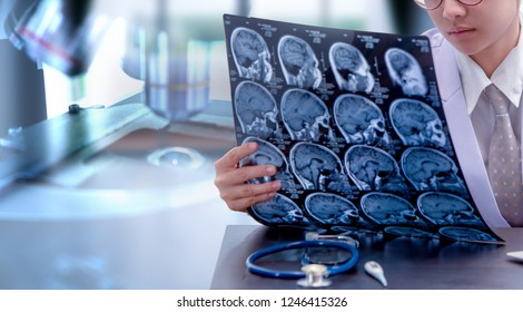 young female doctor holding MRI or CT scan picture, doctor in uniform sitting in working room and holding X-ray picture for diagnosis brain injury or cerebrovascular accident of patient