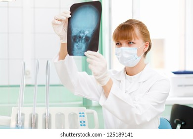 Young female doctor holding a X-ray sheet