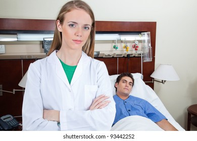 Young female doctor in hospital with patient lying on bed in background