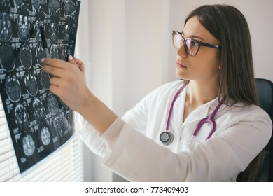 Young female doctor looking at x-ray image. Mri scan, magnetic resonance, radiology