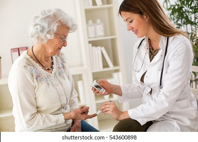 Young female doctor making diabetes blood test on senior woman, closeup