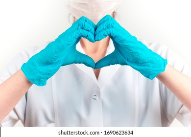 young female doctor in medicine mask is making a heart sign. White background