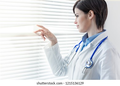 Young female doctor or nurse looking through a window parting the louver blinds with her fingers as she watches something outside