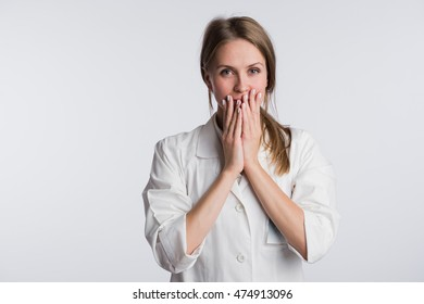 Young female doctor or nurse is shocked with hands on her mouth