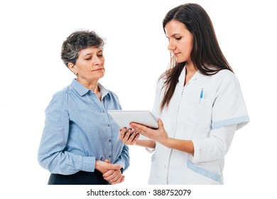 Young female doctor with pad is explaining medication to senior patient - isolated on white
