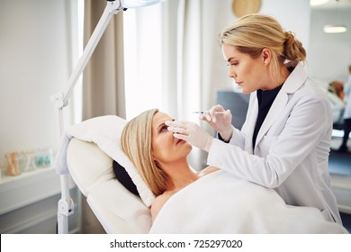 Young female doctor performing injections on the forehead of a mature woman lying on a table in a beauty clinic