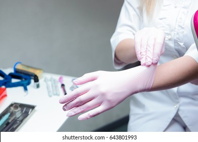 A young female doctor preparing herself for working, putting on protective gloves.
