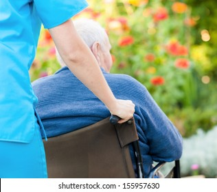 Young female doctor pushing and old patient in wheelchair.