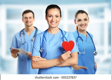 Young female doctor with red heart and medical team on blurred background. Cardiology concept.
