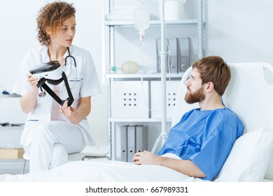 Young female doctor showing VR goggles to young male patient with beard